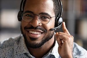 person smiling and taking a call on a headset
