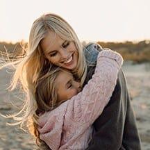 Woman hugging daughter outdoors