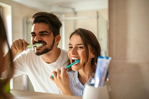 Man and woman brushing their teeth together.