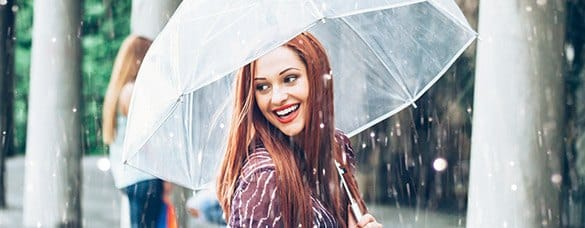 Smiling woman under umbrella